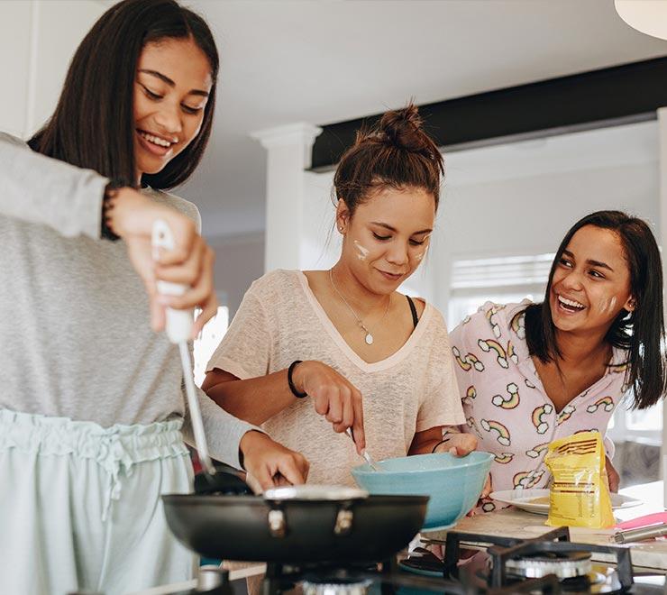 Trois adolescents ensemble dans une cuisine, qui font de la popotte